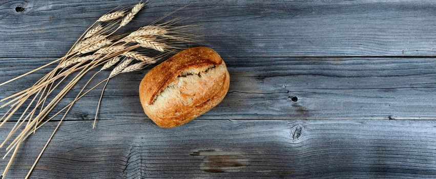 Homemade full sourdough loaf of bread and wheat stalk decorations