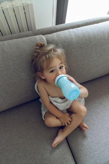 Sweet Adorable Baby Sitting at Home on the Couch and with Pleasure Drinking Formula Milk. Healthy Organic Nutrition for Little Child.
