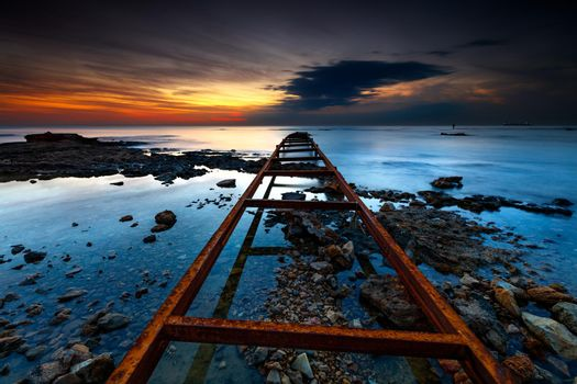 Serene Beach View in Mild Sunset Light. Long Rusty Leading Lines. Bridge Support goes into the Distance of the Sea. Batroun. Lebanon.
