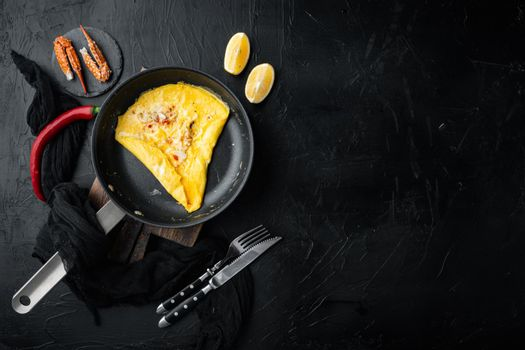 Chilli crab silky omlette , on frying iron pan, on black background, top view flat lay , with copyspace and space for text