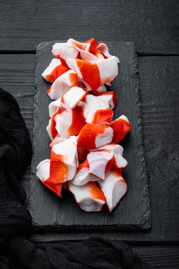 Asian snack surimi, on black wooden table background