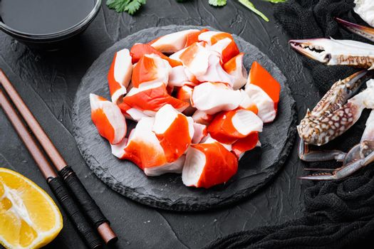 Fresh Crab meat stick surimi with blue swimming crab, on stone board, on black background
