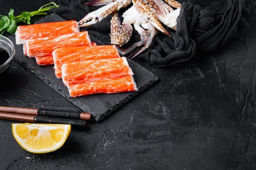 Fresh Crab meat stick surimi with blue swimming crab, on stone board, on black background , with copyspace and space for text