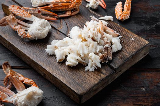 Boiled crab food, on wooden cutting board, on dark wooden background