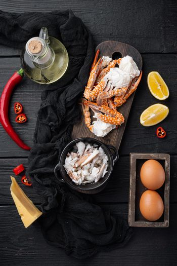 Chilli crab silky omlette ingredients, on black wooden table background, top view flat lay