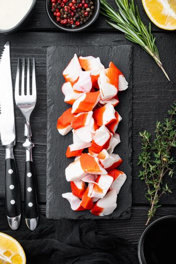 Asian snack surimi, on black wooden table background, top view flat lay