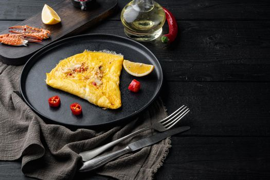 Chilli crab silky omlette , on plate, on black wooden table background