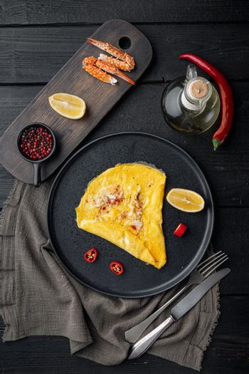 Chilli crab silky omlette , on plate, on black wooden table background, top view flat lay