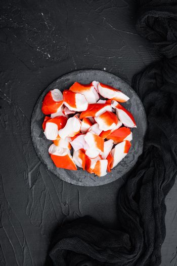 Fresh Crab meat stick surimi , on stone board, on black background, top view flat lay