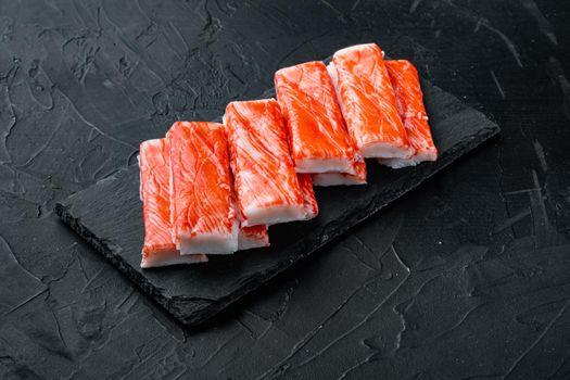 Asian snack surimi, on stone board, on black background