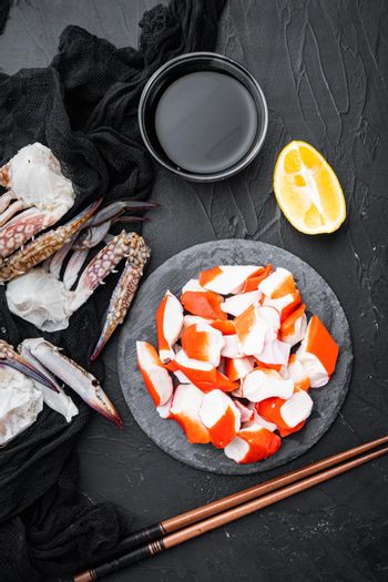 Asian snack surimi, on stone board, on black background, top view flat lay