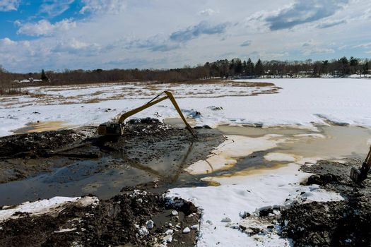Specialized excavator cleans lake sediments of lake bottom on winter