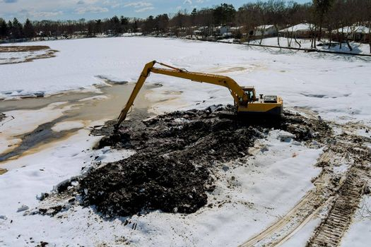 Cleaning the bottom of the lake a excavator bucket is soak in water dredge on winter