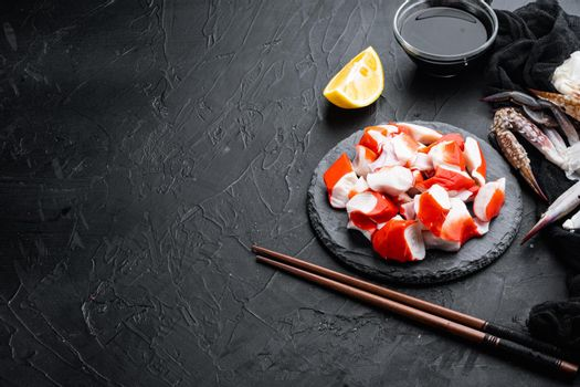 Fresh Crab meat surimi with blue swimming crab, on stone board, on black background , with copyspace and space for text