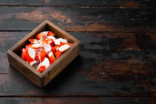 Fresh Crab meat stick surimi with blue swimming crab, in wooden box, on dark wooden background , with copyspace and space for text