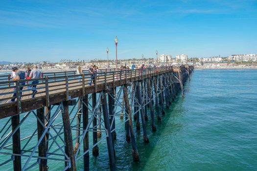 Tourist walking on the Oceanside Pier during blue summer day, Oceanside, northern San Diego, California. Wooden pier on the western United States coastline. Famous for fisher. Febraury 22n, 2020