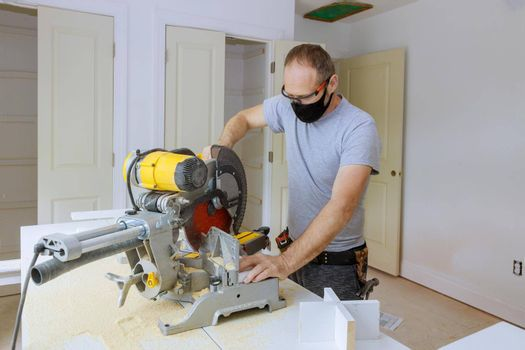 Worker protects himself from covid-19, man cut using circular saw rotating saw cutting wood baseboard