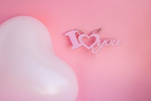 Pink balloon in the shape of a heart on a pink background, with a sign I love you. Wedding concept, Valentine's Day, photo zone, lovers. Banner. top view. Place for your text