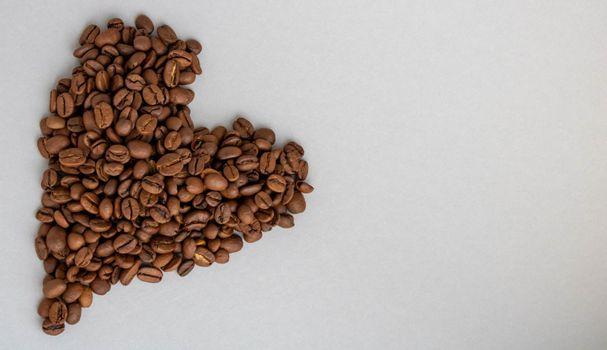 Heart-shaped coffee beans isolated on a gray background. Space for text.