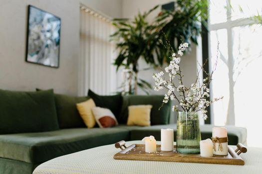 Home interior. Relaxing candles. Apple tree color has flown. Blurred background