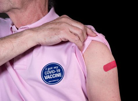 Senior man displaying the adhesive bandage over Covid-19 shot