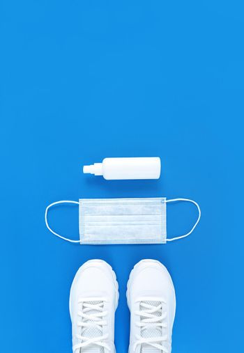 White medical mask, trainers, and hand sanitizer on a blue background. Monochrome vertical flat lay.