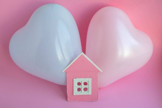 Two balloons and a pink cardboard house on a pink background. Family history in symbols.