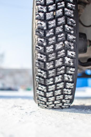 Car tires on the winter road are covered with snow. A car on a snow-covered alley. A car wheel in the snow.