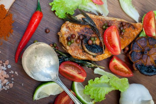 wood fired hoven cooked chicken breast on wood board