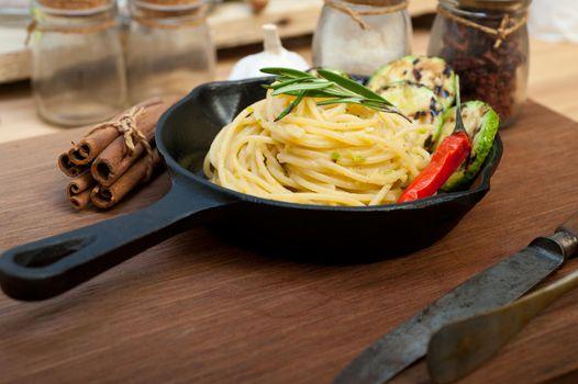 italian spaghetti pasta with zucchini sauce on iron skillet