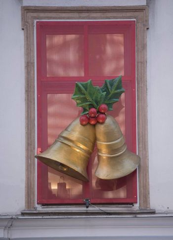 christmas bells and mistletoe hanging in front of a red window
