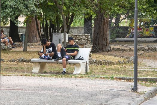 terni,italy august 16 2020:boys at the park with smartphones