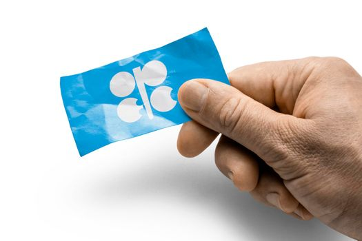 Hand holding a card with a national flag the Organization of the Petroleum Exporting Countries