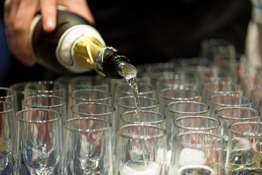 Bartender pouring champagne into glass.