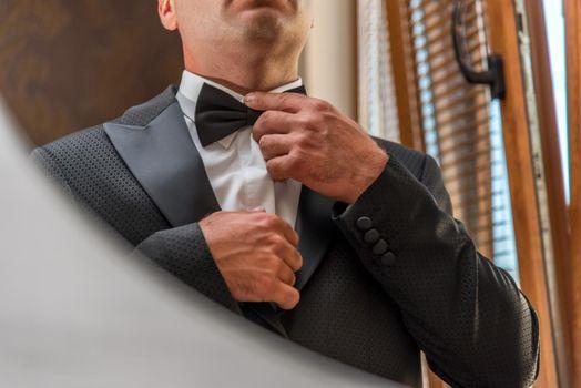 Hispanic man adjusting bowtie