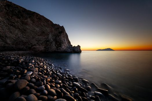 Amazing View of a Sunset Light over the Sea. Beautiful Stony Beach. Peaceful Romantic Resort on an Island. Greece.