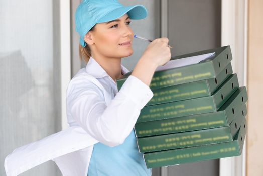 Nice Delivery Girl Wearing Special Uniform Signs a Check for Payment. Delivering Hot Delicious Pizza. Delivery Door to Door. Conceptual Photo of a Service Occupation.