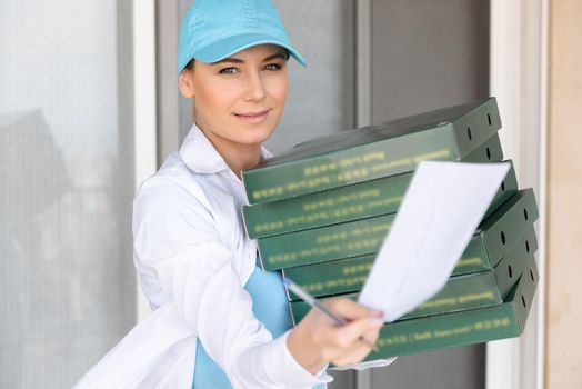 Portrait of a Pretty Girl Wearing Uniform Delivering Pizza to the Customer. Service Occupation. Fast Food. Tasty Eating. Summer Job. Door to Door Delivery.