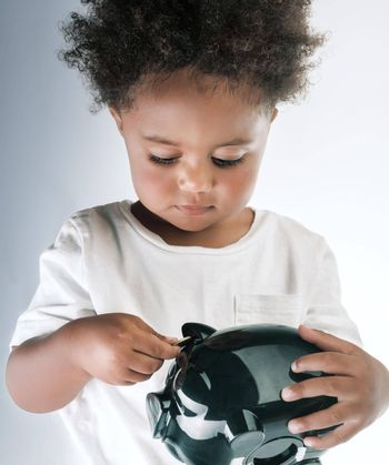 Portrait of a Cute Little African American Boy With Piggy Bank in Hands. Isolated over Empty Gray White Background. Investment in the Future. Saving Money Concept.