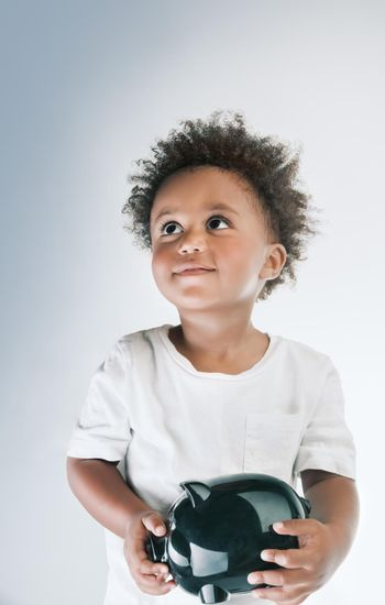 Portrait of a Cute Little African American Boy Model With Piggy Bank in Hands. Isolated on Clean Gray White Background. Investment in the Future. Saving Money Concept.