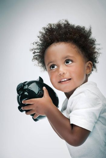 Portrait of a Cute Little African American Boy Shakes his Piggy Bank and Checks How Many Coins he Has. Isolated on Grey White Background. Happy Childhood.