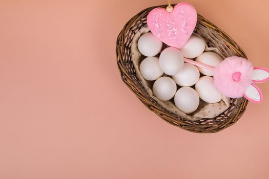 Easter. White eggs in a basket with an artificial rabbit, on a uniform pink background. Place for text.