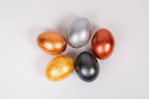 Easter. Multi-colored eggs on a uniform white background with place for text. View from above.