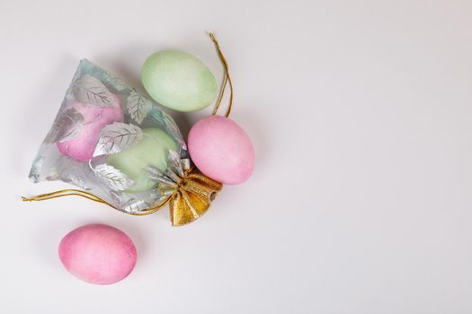 Easter. Eggs of different colors in a bag on a uniform blue background. Place for text.