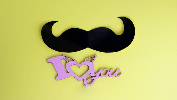 Father's Day concept. Black mustache and I love you sign on yellow paper background.