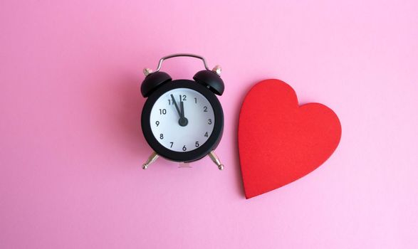 Black vintage alarm clock and red wooden heart lying on pink background.