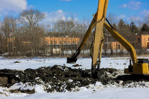 Excavators dredge and clean up a lake the winter snow of lake bottom