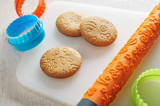 Cookies, embossing rolling pin and cookie cutters on a white cutting board
