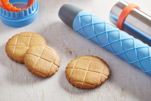 Cookies, embossing rolling pin with checkered pattern and cookie cutters on a white wooden surface