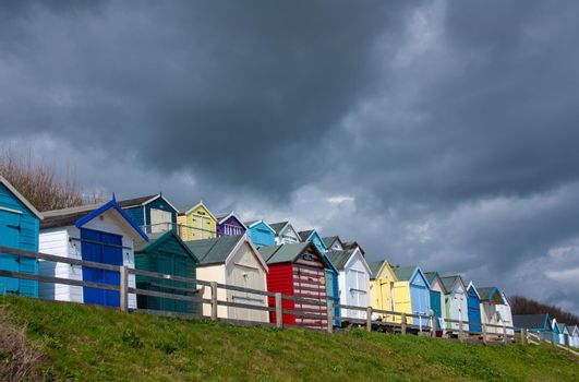 row of beach huts with a deep blue sky, colourful beach huts